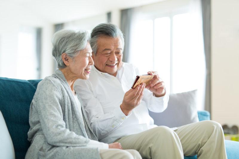 老人ホーム 何歳から-スマホをみるシニア夫婦