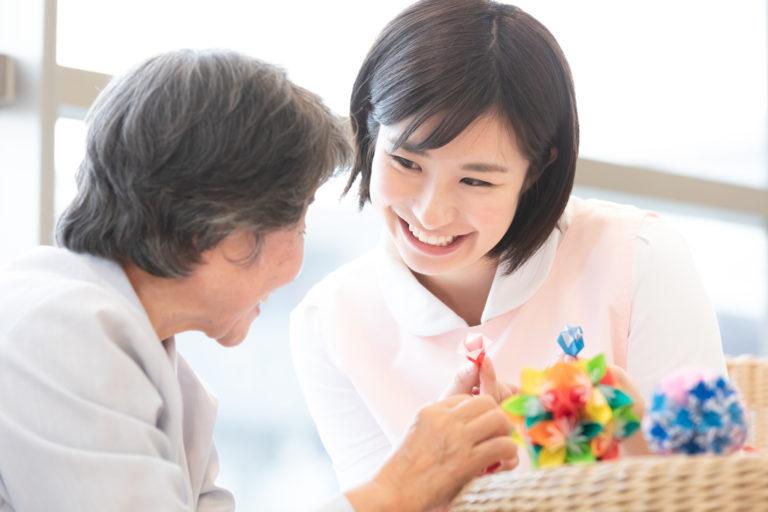 老人ホーム ボランティア‐折り紙をする高齢者と介護士