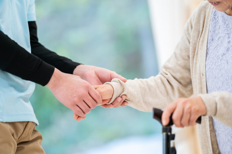 老人ホーム ボランティア-老人に手を添える介護スタッフ