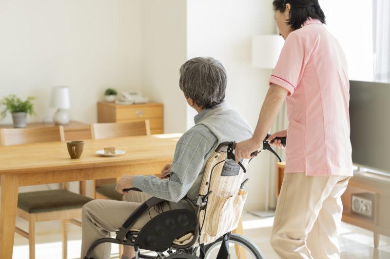 老人ホーム 退去‐車いすに乗りながら介護される人の後ろ姿