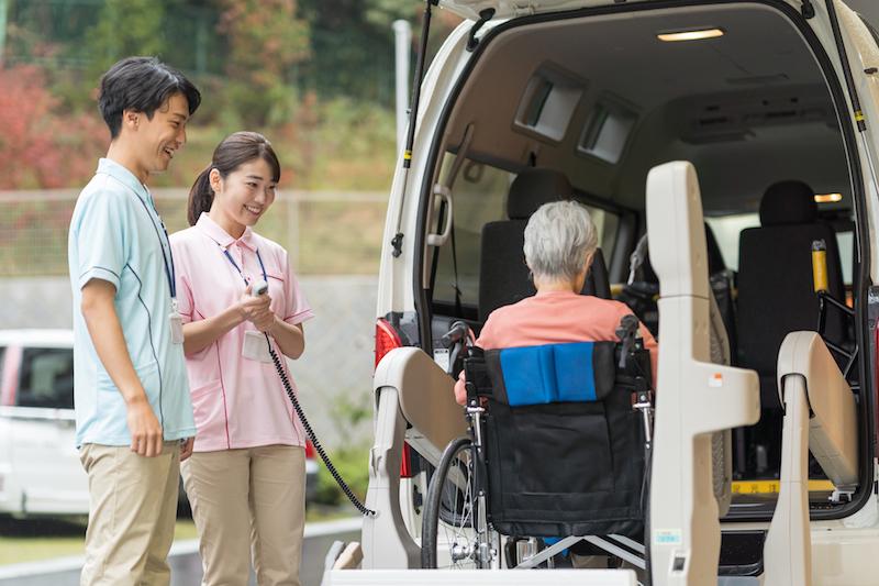 デイケア 料金-介護施設の送迎車に乗る車イスの高齢者