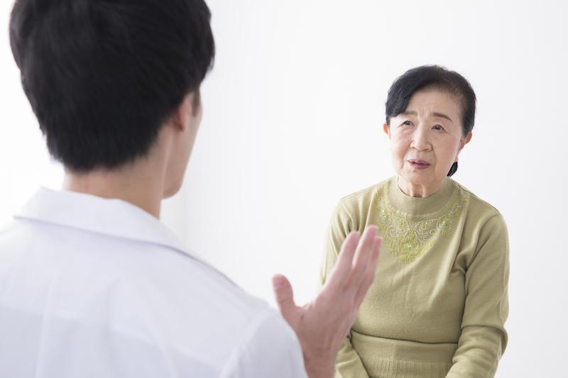 認知症 症状-医師と話すシニア