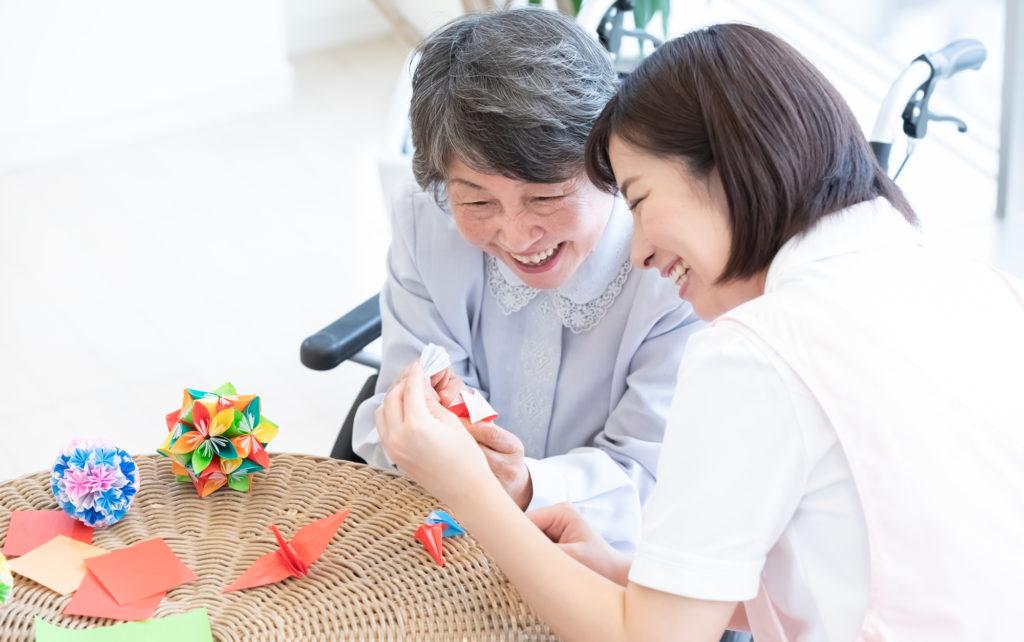 老人ホーム レクリエーション-折り紙を折る介護スタッフと高齢者