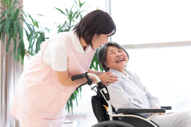 親の介護したくない-車イスの女性と楽しく話をする介護士