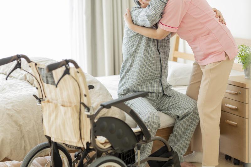 老人ホーム 罪悪感-ベットから起き上がる時に介護されている高齢者
