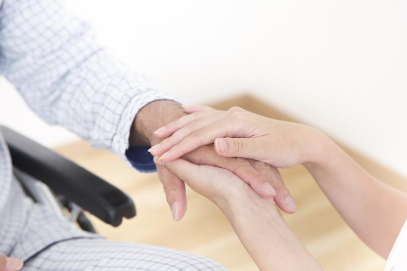 要介護2 施設-手を合わせる介護士とシニア