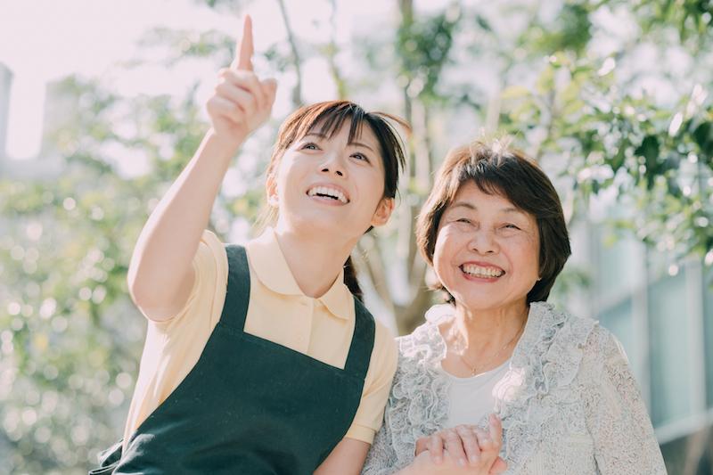 介護 介助 違い-笑いあう介護士とシニア女性