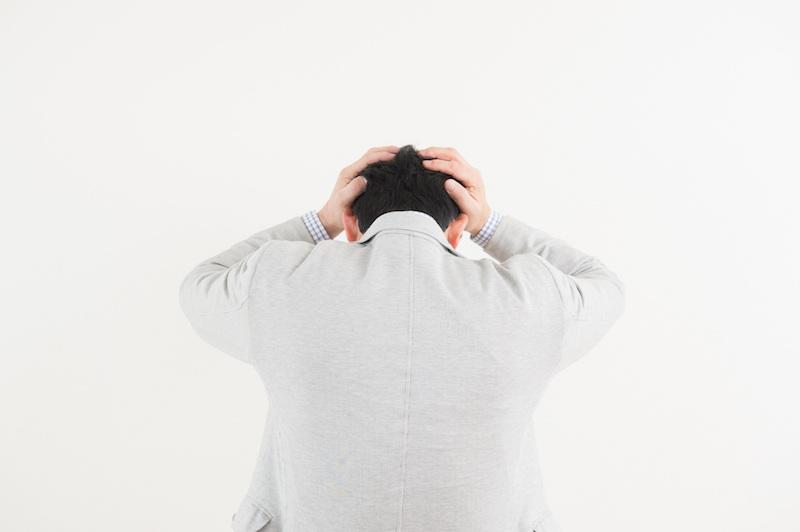 認知症 被害妄想-頭を抱えるシニアの後ろ姿