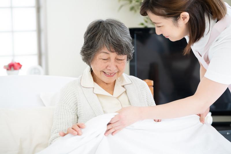 定期巡回・随時対応型訪問介護看護とは-ベッドに座るシニアとヘルパー
