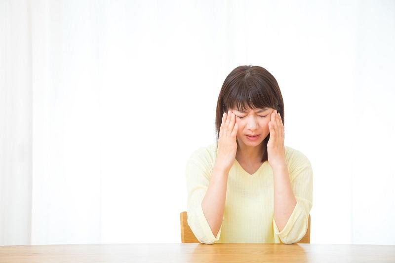若年性認知症 症状-こめかみを押さえて考え事をする女性