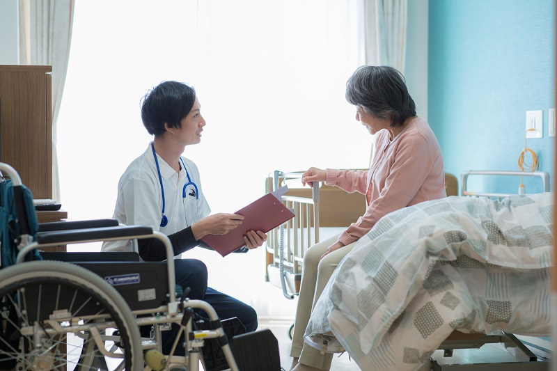 胃ろう デメリット-ベッドに座るシニア女性と医療スタッフ