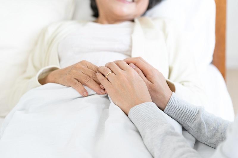 ベッドに横たわるシニア女性の手を握る