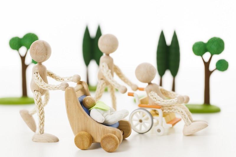ダブルケアの経験談-車イスとベビーカーを押す木の人形