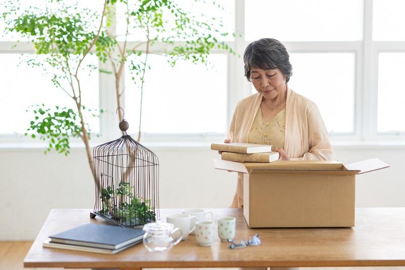 環境整理収納術-ダンボールに物を詰めるシニア女性