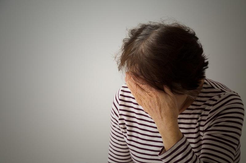 認知症 被害妄想-額に手を当てるシニア女性