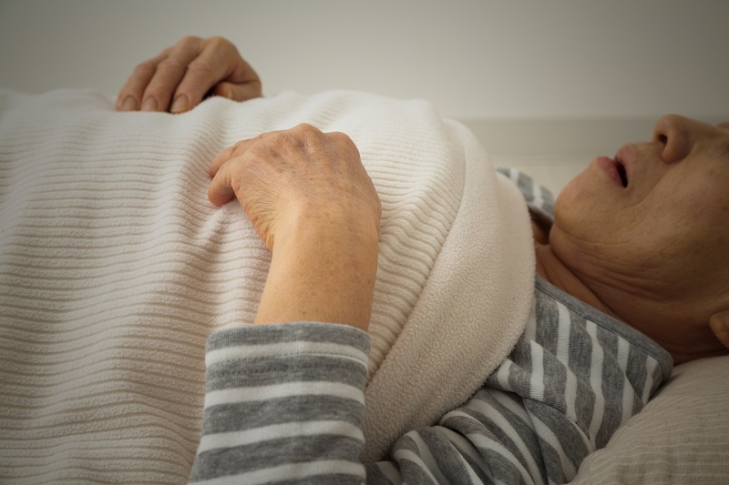 孤独死 対策-ベッドで寝っ転がるシニアの上半身