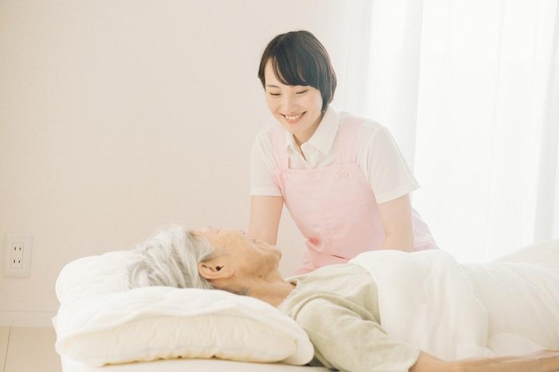 要介護5 自宅介護-寝たきりのシニア女性とヘルパー