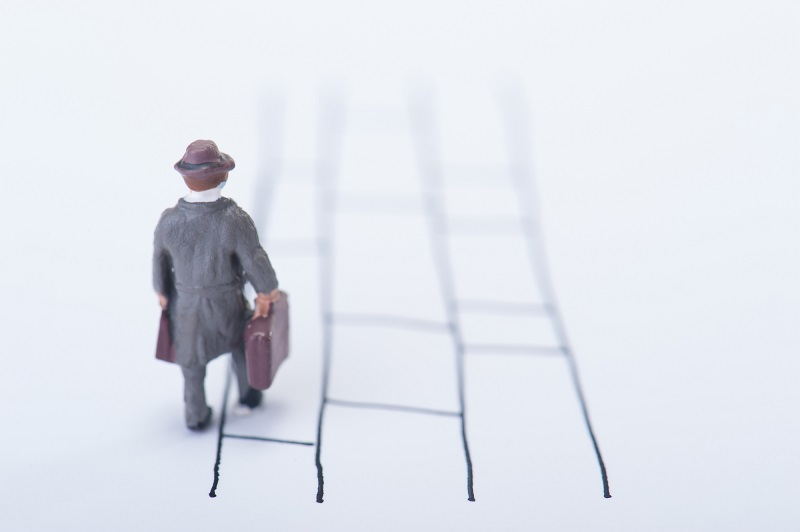 終活について-あみだくじの上を歩く男性の人形