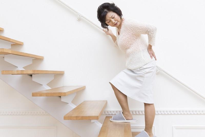 ロコモティブシンドローム 原因-手すりを掴んで階段を登るシニア女性