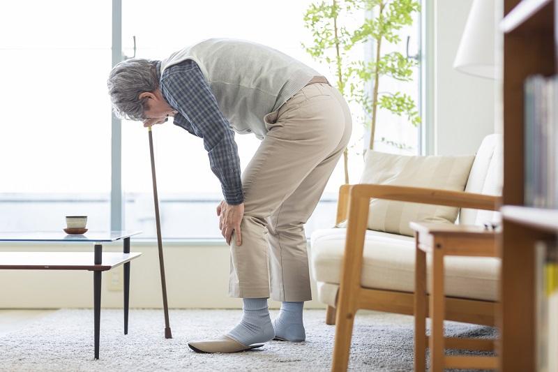 ロコモティブシンドローム 原因-膝を抑える杖をもったシニア男性